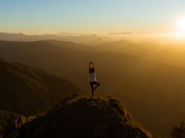 A young woman does a tree yoga pose while standing on a small mountain overlooking rolling foothills as the sun sets