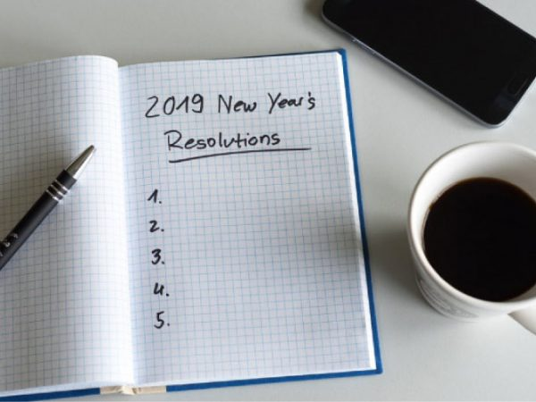 2019 new year's resolutions notebook, a pen, cup of coffee and a cell phone