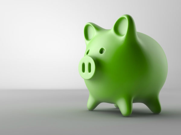 Green piggy bank on a gray counter to represent greedy corporate dentistry