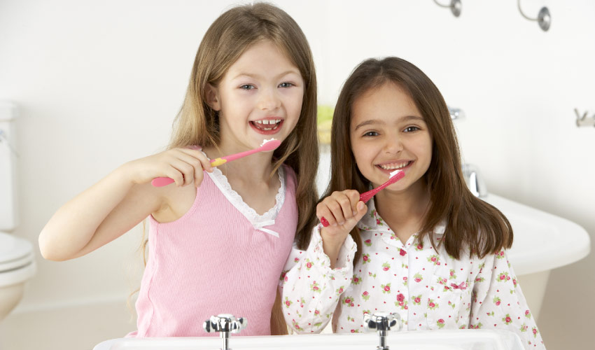 two young girls brushing their teeth