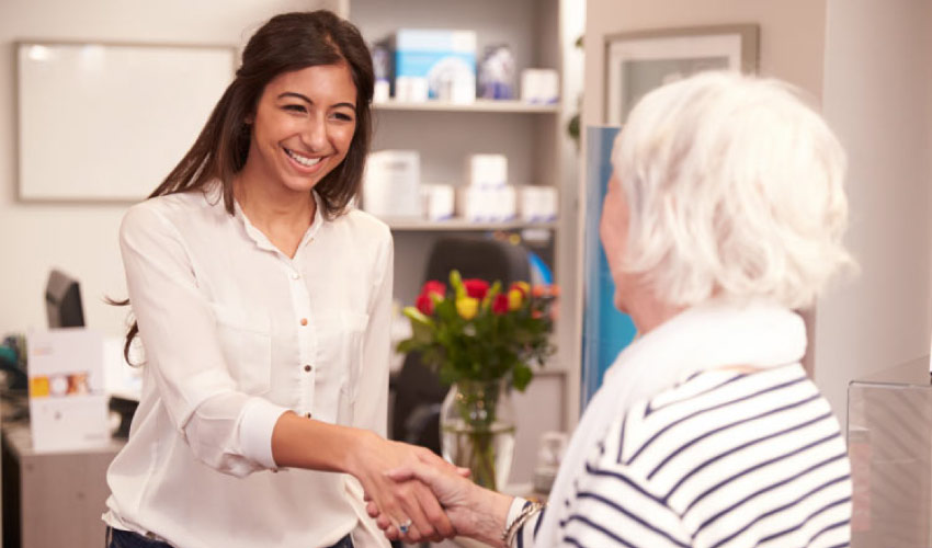 dental receptionist greets a patient with a smile and a handshake