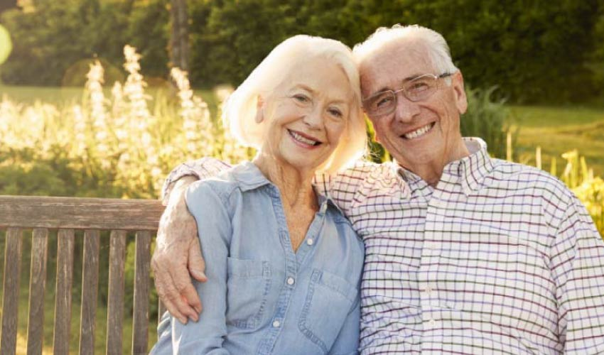 senior couple sitting on a bench smiling after learning about the longevity of their dental implants