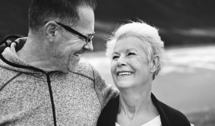 senior couple smile at each other after learning about dental crowns